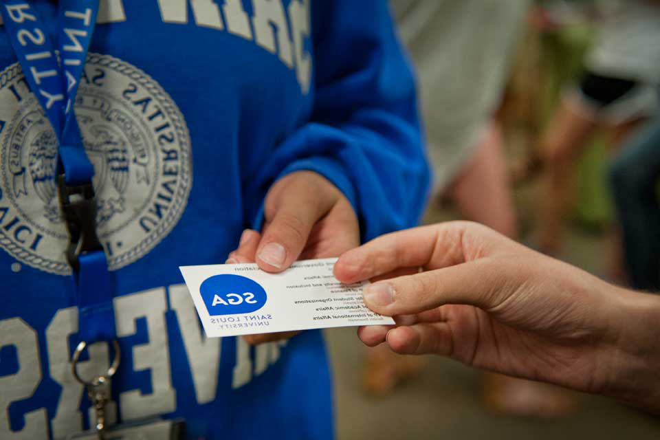 Student holding a SGA business card